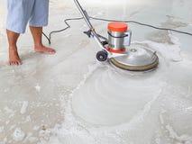 Arbetare som använder skurborstemaskinen för rengörande och polerande golv royaltyfria bilder