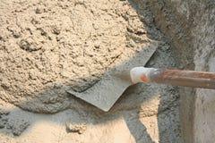 Arbetare som använder skyffeln för att blanda betong, sand, vaggar och bevattnar i den enorma svarta plast- bunken royaltyfria bilder