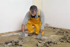 Arbetare som använder spackeln för rengörande golv arkivfoto