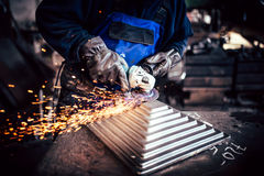 Arbetare som använder vinkelmolar för klippande och avslutande stål Arkivfoton
