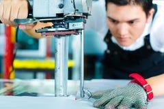 Arbetare som använder en bearbeta med maskin i kinesisk fabrik Arkivbild