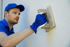 Arbetare som applicerar dekorativ fasadmurbruk på husväggen royaltyfri fotografi