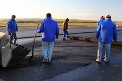 Arbetare som applicerar förstärkningen, kopplar ihop på en yttersida i förberedelsen för att stenlägga Arkivfoton