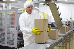 Arbetare som arbetar på emballagelinje i fabrik Arkivbild