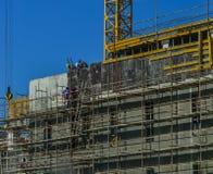Arbetare som arbetar på modern konstruktionsplats arkivfoton