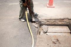 Arbetare som arbetar på vägplatsen som demolerar asfalt med pneumat fotografering för bildbyråer