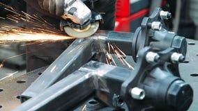Arbetare som bearbetar stället av rör för fyrkant för svetsningsmetall med vinkelmolar stock video