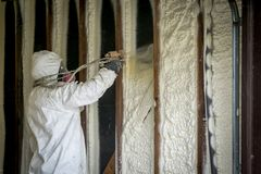 Arbetare som besprutar stängd isolering för cellsprejskum på en hem- vägg arkivfoton