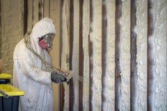 Arbetare som besprutar stängd isolering för cellsprejskum på en hem- vägg arkivbilder