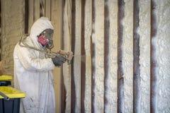 Arbetare som besprutar stängd isolering för cellsprejskum på en hem- vägg arkivbild