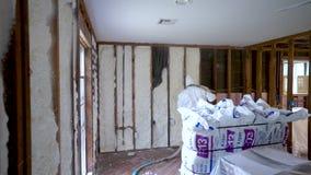 Arbetare som besprutar stängd isolering för cellsprejskum på en hem- vägg arkivfilmer