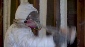 Arbetare som besprutar stängd isolering för cellsprejskum på en hem- vägg lager videofilmer