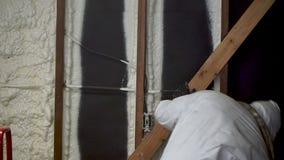 Arbetare som besprutar stängd isolering för cellsprejskum på en hem- vägg stock video