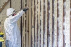 Arbetare som besprutar stängd isolering för cellsprejskum på ett hem arkivbilder