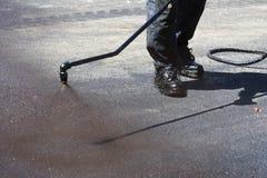 Arbetare som besprutar varm asfalt Royaltyfria Foton