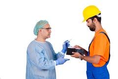 Arbetare som betalar kirurgiavgiften till kirurgen som isoleras på vit bakgrund Arkivfoto