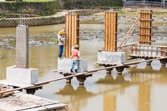 Arbetare som bygger brofundamentet över sjön royaltyfria foton