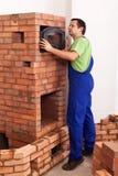 Arbetare som bygger en murverkvärmeapparat royaltyfri bild