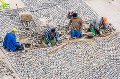 Arbetare som bygger vägstenläggning i Buda Castle. Royaltyfri Fotografi