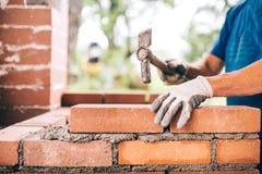 Arbetare som bygger yttre väggar, genom att använda hammaren för att lägga tegelstenar i cement Detalj av arbetaren med hjälpmede Royaltyfri Fotografi