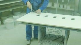 Arbetare som dammar av ett ark av kryssfaner, innan att måla Trämöblemang för fabrik för tillverkning av arkivfilmer