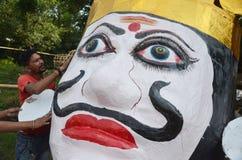 Arbetare som förbereder ett huvud av gigantisk formatavbildning av den hövdade konungen Ravan för demon tio i Bhopal Arkivfoto
