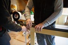 Arbetare som förbereder sig att installera nya träfönster arkivfoto