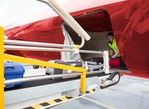 Arbetare som förlägger bagage på transportör, medan lasta av flygplanet Royaltyfri Fotografi
