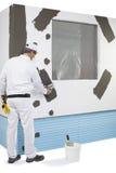 Arbetare som förstärker en fönsterram Royaltyfri Foto