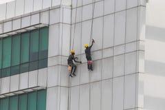 Arbetare som gör ren eller målar en flervånings- byggnad Arkivfoto
