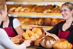 Arbetare som ger brödkorg till den kvinnliga kunden royaltyfri fotografi