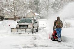 Arbetare som gör klar snö med blåsare- och snöplogen Arkivfoto
