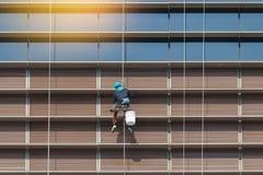 Arbetare som hänger det utvändiga höga fönstret och spegeln för löneförhöjningbyggnadslokalvård arkivbilder