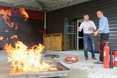 2 arbetare som i fall att utbildar brandnödläge Royaltyfri Fotografi