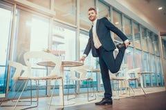Arbetare som i regeringsställning sträcker benet på tabellen royaltyfri fotografi