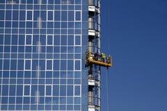 Arbetare som installerar det glass fönstret Arkivfoto