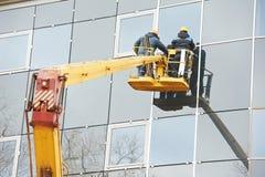Arbetare som installerar det glass fönstret på byggnad Royaltyfri Fotografi