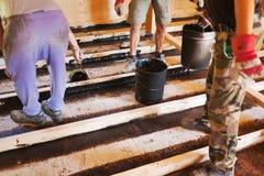 Arbetare som installerar ett husfundament Arkivbild