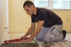 Arbetare som installerar golvtegelplattor Keramiska tegelplattor och hjälpmedel för tiler Fotografering för Bildbyråer