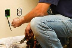 Arbetare som installerar kabel inom väggen Arkivbild