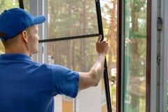 Arbetare som installerar myggnättrådingreppet i plast- fönsterram arkivbilder