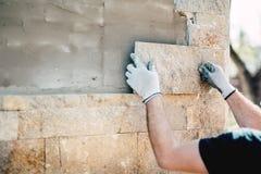 Arbetare som installerar stenen på arkitektonisk fasad av nybygge Detaljer av konstruktionsbransch royaltyfri bild