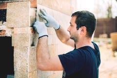 Arbetare som installerar stenen på arkitektonisk fasad av nybygge Detaljer av konstruktionsbransch arkivbild