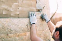 Arbetare som installerar stentegelplattor på väggen på konstruktionsplats royaltyfri bild