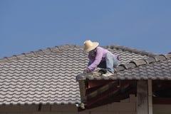 Arbetare som installerar taktegelplattor för hem- byggnad arkivfoto