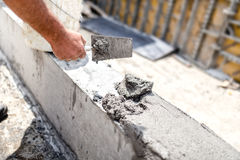 Arbetare som jämnar betong med spackeln på byggnadsplatsen Detaljer av konstruktionsbransch Royaltyfri Bild