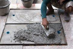 Arbetare som jämnar cement av avrinningslangen med mursleven fotografering för bildbyråer