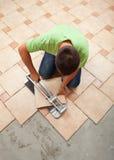 Arbetare som klipper den keramiska golvtegelplattan Arkivbild