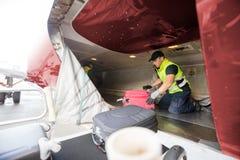Arbetare som knäfaller, medan lasta av flygplanet Royaltyfri Foto