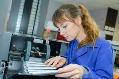 Arbetare som kontrollerar den utskrivavna frågan som är kommande av press Royaltyfria Foton